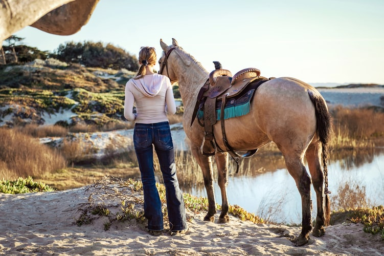 woman-facing-away-from-camera-while-standing-next-to-horse-wearing-western-saddle-on-beach